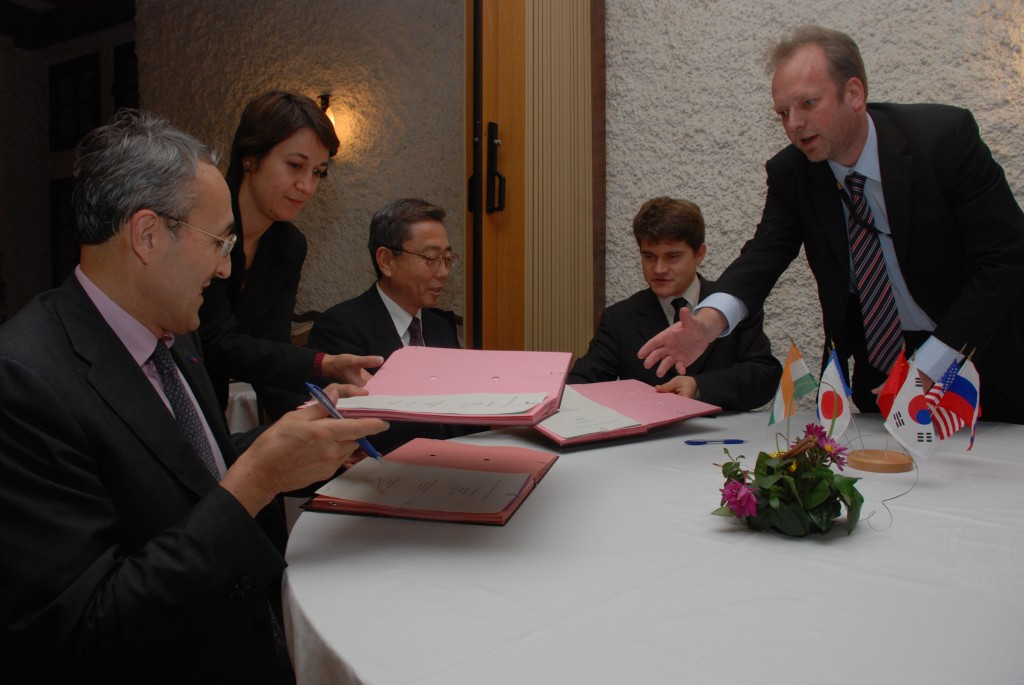 Kaname Ikeda, Bernard Bigot and François Gauché signing the Site Support Agreement. Akko Maas and Laetitia Grammatico assist with the documents.