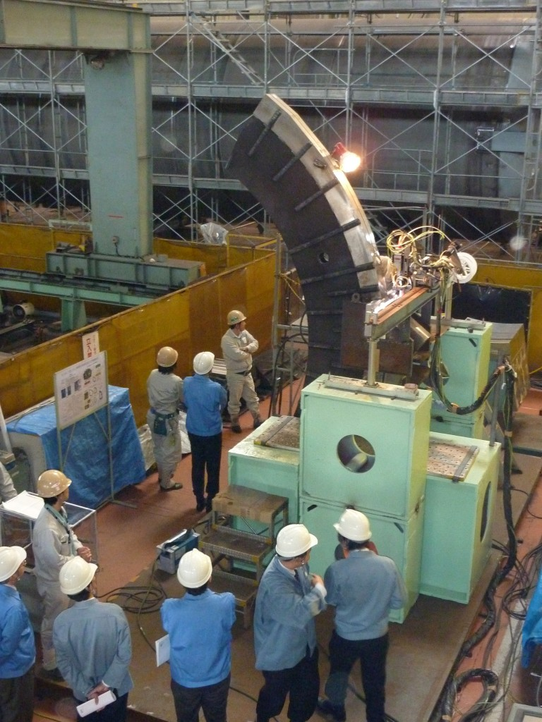 Technicians are busy with welding trials for the pre-compression ring flange that will be attached to the coil cases. (Click to view larger version...)