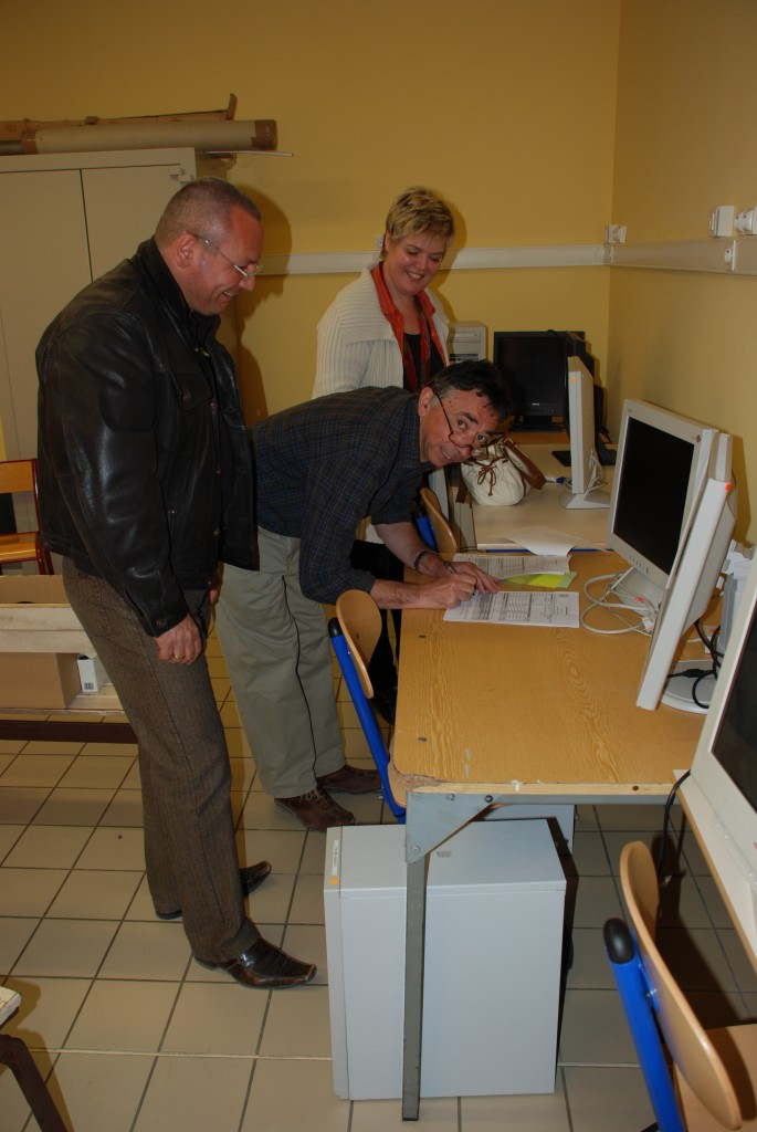 Eric Benoit and Nadine Utzel from the ITER team handing over the computer to school director André Barlatier.  (Click to view larger version...)