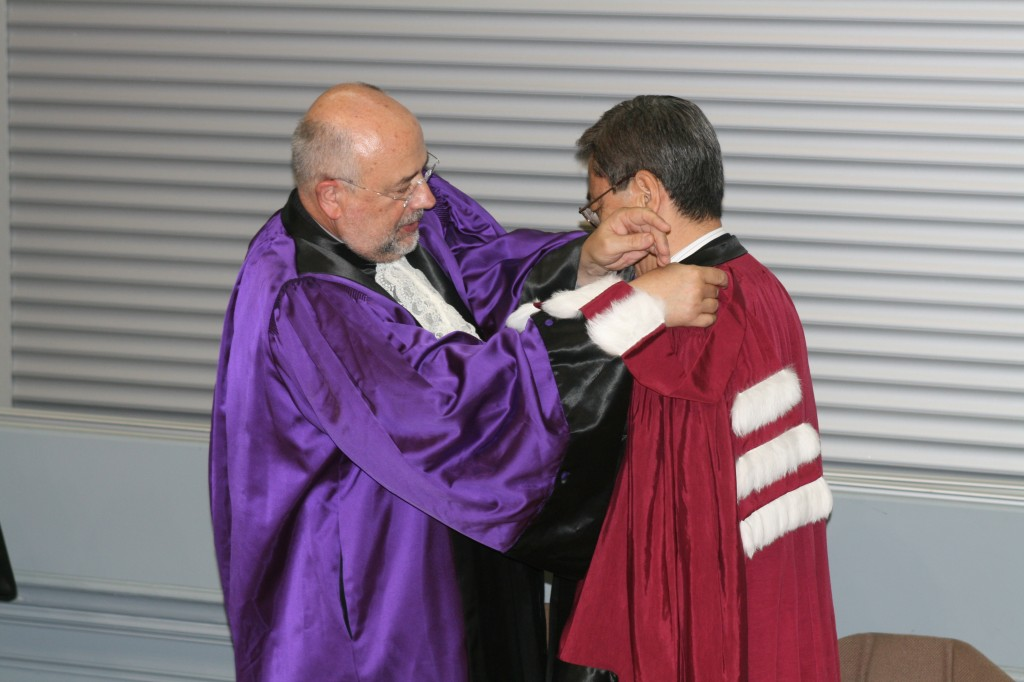 "Jean-Paul Caverni, president of the Université de Provence, attaches the ""ermine sash"" to Director-General Ikeda's purple toga—thus making him a ""Docteur honoris causa."""