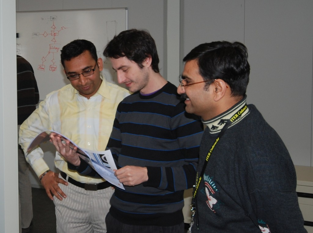 Charad Dhavel (left), Frederic Carayon (middle), and Patel Vijay (right) peruse a preliminary handbook for the new database system.