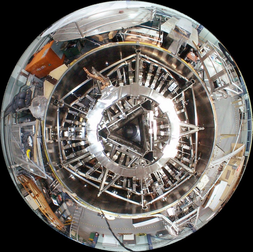 Fisheye view of H-1 from above. H-1 is the National Plasma Fusion Research Facility located at the Australian National University's Research School of Physics and Engineering. H-1 is a 3-period heliac type of stellarator (i.e. one with a helical magnetic axis) with a major radius of 1 m and a mean minor radius in the range 0.15 - 0.2 m. Its construction makes it a highly flexible experimental apparatus. (Click to view larger version...)